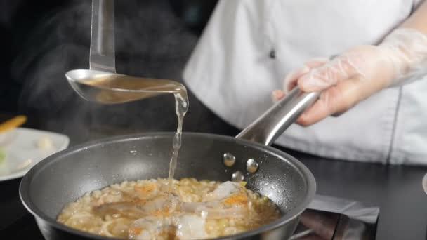 Finom tengeri rizottót sütök serpenyőben. Lassított felvételen. A hallevest merőkanálból öntik ki. Hagyományos olasz konyha. Teljes hd