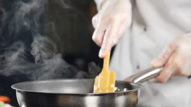 Vaření jídla v restauraci. Zpomalené video. Ženské kuchařky v rukavicích a bílé uniformě míchající jídlo s pádlem na pánvi. Tradiční středomořská kuchyně. Full hd