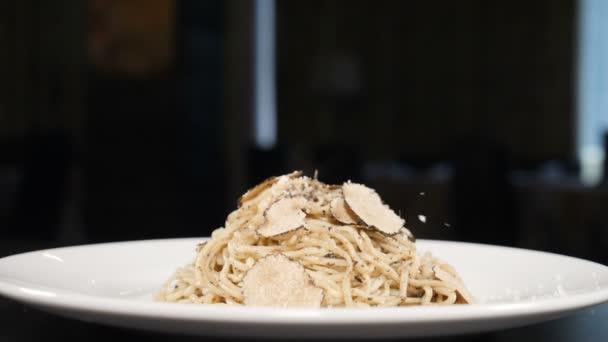 Šéfkuchař sype parmezán na špagety těstoviny v kuchyni restaurace. Složky jídla ve zpomaleném filmu. Italská kuchyně. Parmezán padá na špagety. Posypeme těstoviny strouhaným sýrem. Full