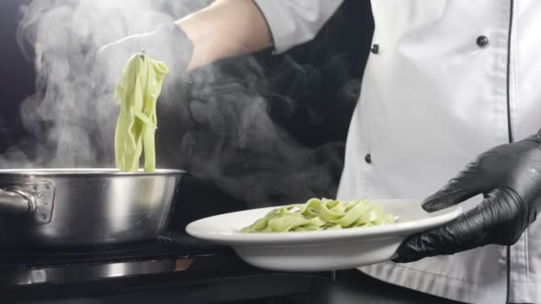 Tésztát főzök az olasz étteremben. A séf főtt tésztát szolgál fel tányéron. Lassú mozgás. Gőz vagy fehér gőz emelkedik a feketére. Olasz konyha. Tésztát teszek a tányérba konyhai nyelvekkel. Teljes hd