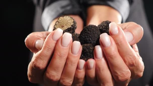 Elegante weibliche Hände, die schwarze Trüffelknollen halten und anbieten. Seltener schwarzer Trüffelpilz auf dunklem Hintergrund. Nahaufnahme. Luxuriös teures Essen, Gourmet im Restaurant. 4 k Video