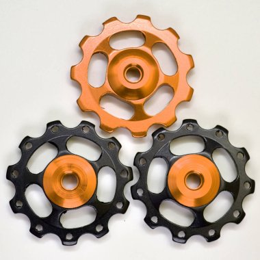 Three color rollers, black, golden gears for bicycle rear derailleur on a white background