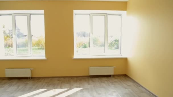 Large yellow empty room with three large windows after repair and restoration