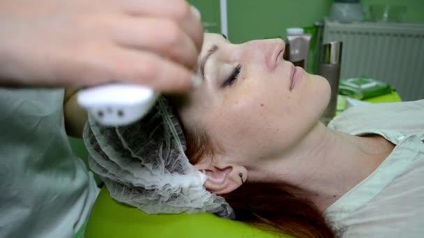 Kosmetikerin trägt mit Hilfe eines Geräts eine pflegende Creme auf das Gesicht der Frau auf