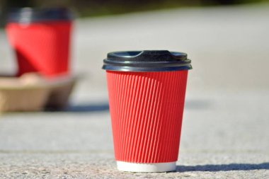 One red paper coffee cup with a black lid stands on concrete surface on a blurred background of other glasses