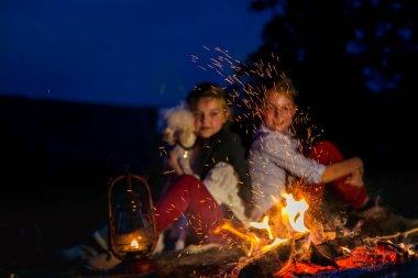 Köpekli kızlar ateşin yanında ısınıyor..