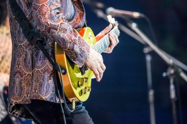 Finger style guitar, from experience expertist artist with colorful suit.