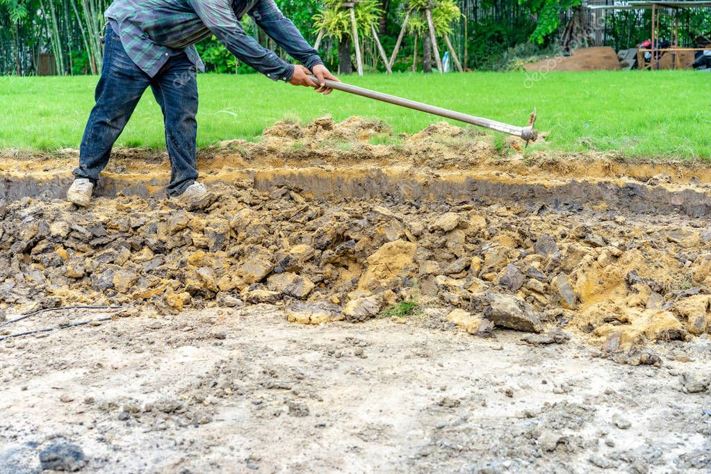 gardener digs the soil with his equipment for gardening and prepare land for plantation.