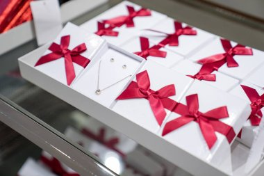 Pendant and earring in the paper box with red bow are display fo