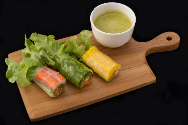 Fresh vegetable noodle spring roll with sauce on wooden tray, Salad roll, On a black background. Diet or cook concept.