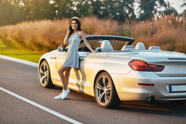 full length shot of cheerful woman leaning the cabrio on the country road