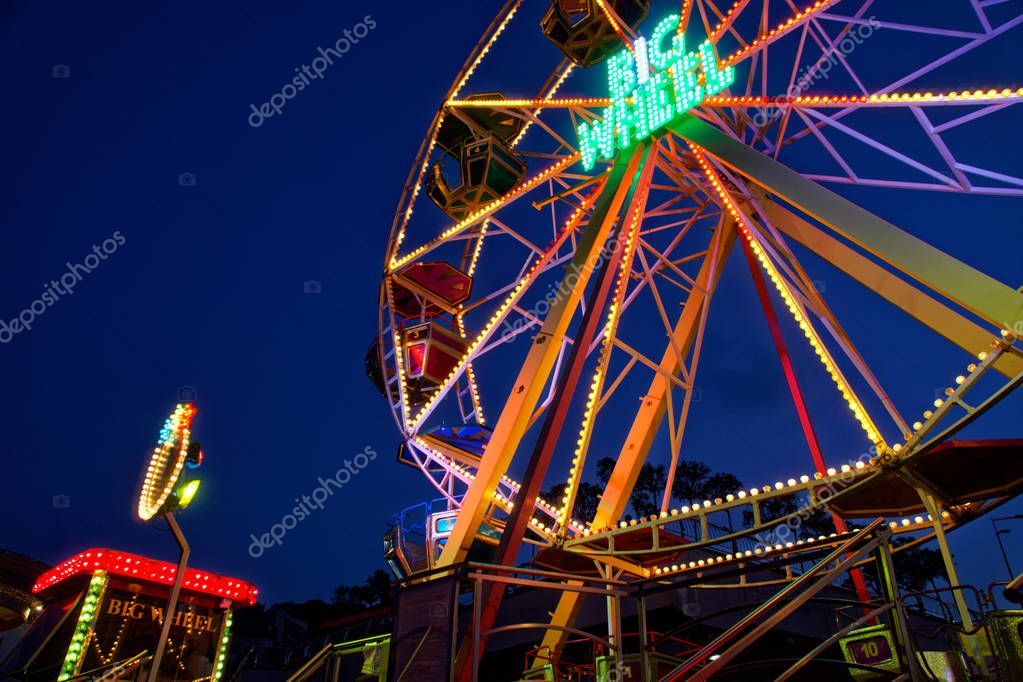 Kyiv - Ukraine, Poshtova square, 13.08.2018: Ferris wheel attraction illuminated with colorful lights in motion