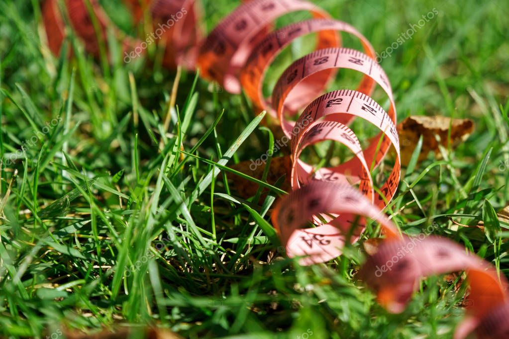 Fit centimeter on green grass measuring tape