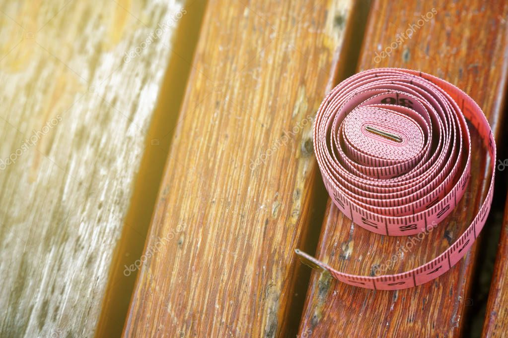 Fit centimeter on wooden bench measuring tape foe sport background