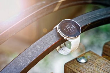 Sport watch for running white color on wooden bench. Fitness watch for tracking daily activity and power training.