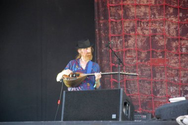 Trencin, Slovakia - July 9, 2011: Lu Edmonds playing bouzouki live with Public Image limited (PIL, ex Sex Pistols) at Pohoda Festival with Johnny Rotten