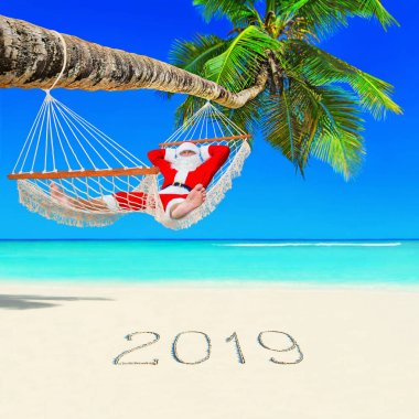 Santa Claus relax in mesh hammock under coconut palm tree at tropical ocean island beach with 2019 handwritten caption on white sand. Happy New Year and Merry Christmas travel destinations concept