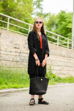 beautiful girl with long hair in sunglasses with bag in long dark clothes