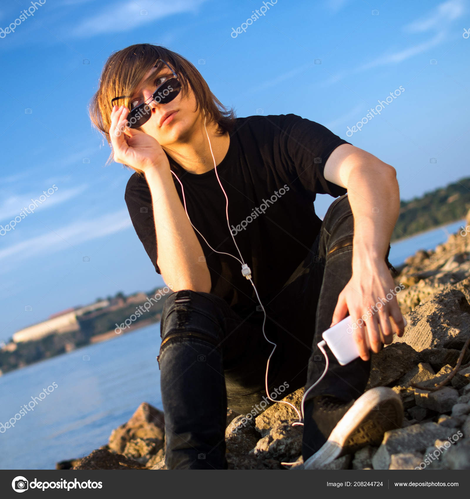 Teenage boy hanging out alone riverside listening music mobile phone stock photo