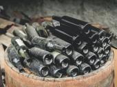 Detailní záběr z prázdné špinavé použitých lahví vína na hromadu v dřevěný Sud v Gruzii