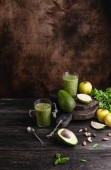 Fotografie Organic smoothie on rustic table with fruits and herbs