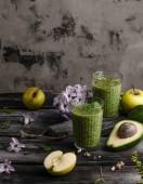 Vynikající detoxikační koktejl na rustikální dřevěné desce s ovocem a květiny