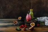 Friss egészséges smoothies, a rusztikus asztal bogyók és a golgotavirág gyümölcse