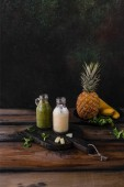 Fotografie Delicious detox smoothies with tropical fruits on rustic wooden board