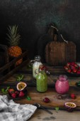 Fotografie Fresh healthy smoothies on rustic table with exotic fruits