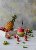 Fotografie Organic layered fruit smoothie on wooden background with exotic fruits