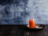 Photo Fresh orange smoothie in bottle on rustic table