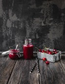 Fotografie Fresh healthy smoothie on rustic table with cherries and straws