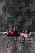 Fotografie Ripe berries and delicious detox smoothie on rustic wooden board