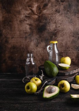 Glass bottles and fruit ingredients for smoothie on rustic wooden board