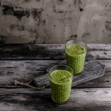 Organic green smoothie in glasses on wooden table