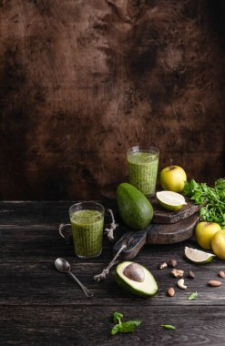 Organic smoothie on rustic table with fruits and herbs