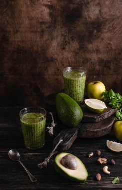 Fresh healthy smoothie on rustic table with fruits and herbs