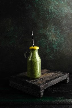 Delicious detox smoothie in bottle with lid on rustic wooden board