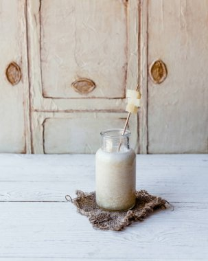Delicious detox smoothie in glass bottle on white wooden board