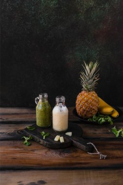 Delicious detox smoothies with tropical fruits on rustic wooden board