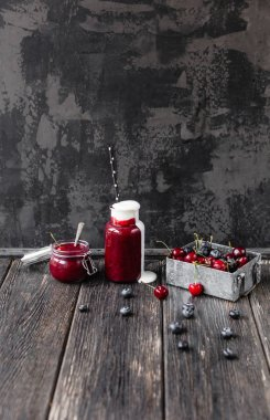 Organic berry smoothie in bottle and jar on wooden background
