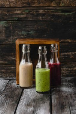 Organic fruit smoothies in glass bottles on wooden background