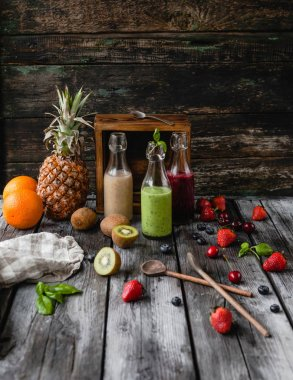 Delicious detox smoothies in glass bottles on rustic wooden board with assorted fruits