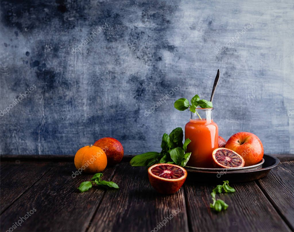 Delicious blood oranges juice in glass on rustic wooden board