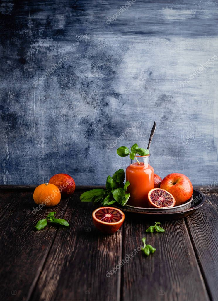 Organic blood oranges juice in glass on wooden background