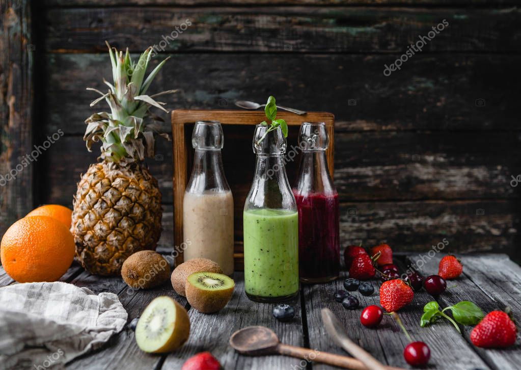 Organic fruit smoothies in glass bottles on wooden background with assorted fruits