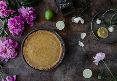 top view of tasty lemon pie and violet peonies on wooden table