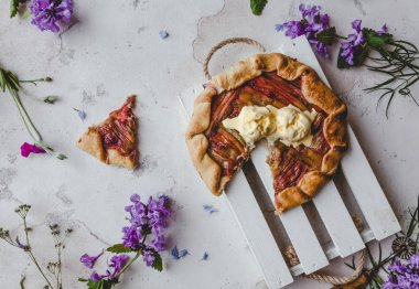 elevated view of delicious rhubarb pie on table with violet flowers