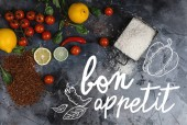 Photo top view of raw rice in container, spices and vegetables on scratched grey surface, bon appetit lettering