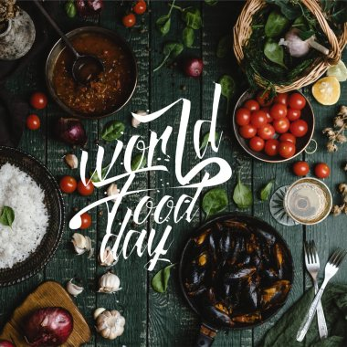Top view of cooked mussels with shells served in pan with tomatoes, herbs and wine on wooden table, world food day lettering